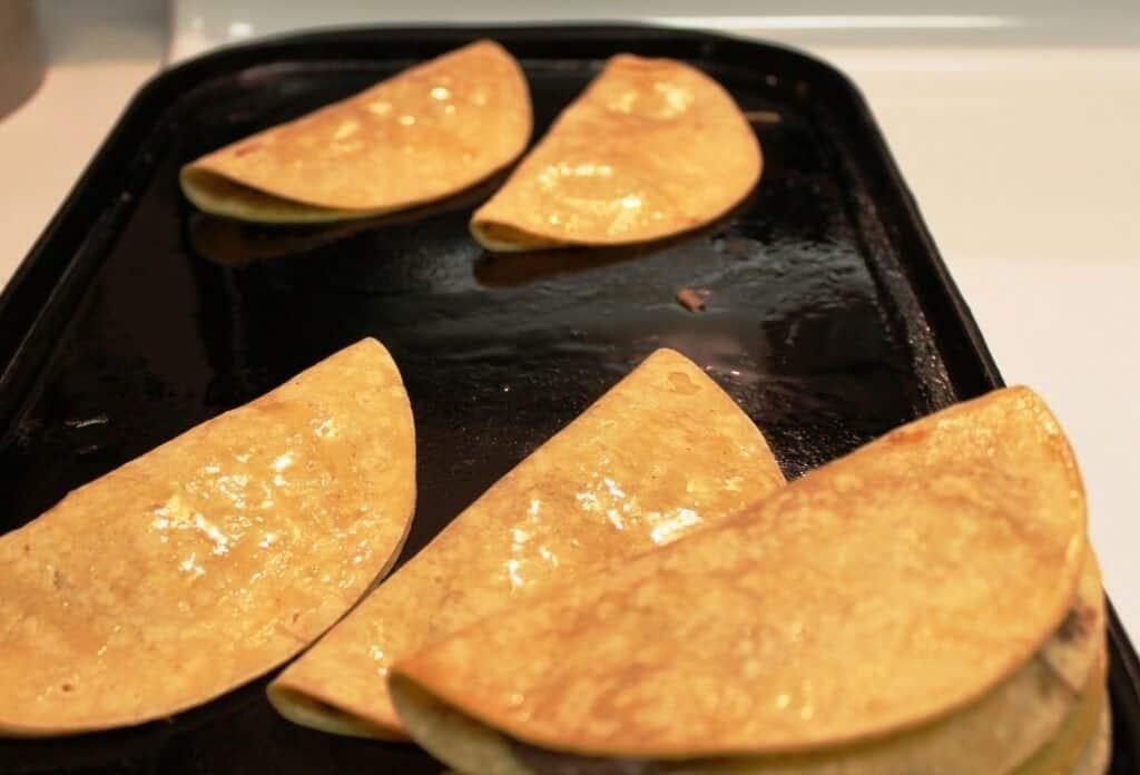Cachetadas tacos de Tampico, coloca las tortillas dobladas en la sartén o comal